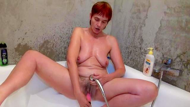 Old redhead granny is fucking her hairy snatch