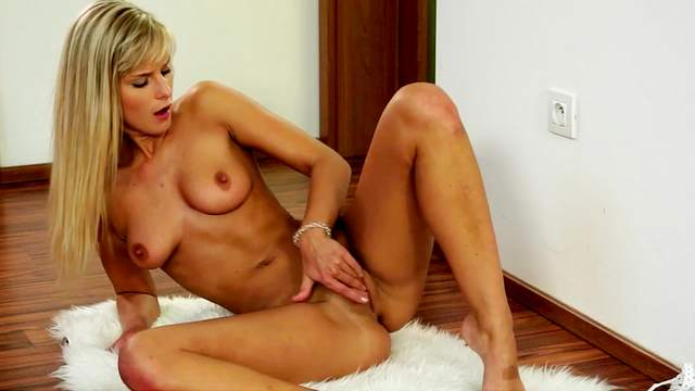 Tanned Miela is posing naked and touching her puss