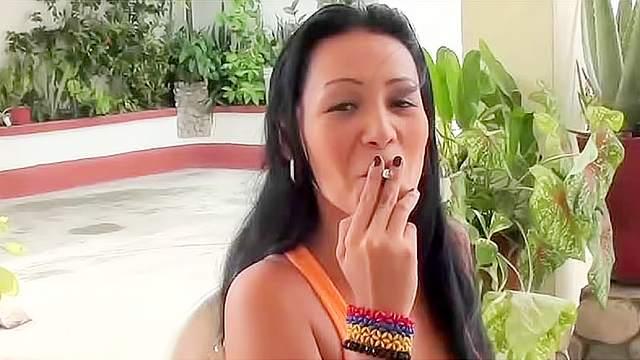 Handsome brunette is smoking cigarette outdoors
