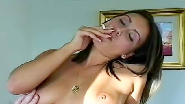 Nude and happy brunette is smoking cigarette after work